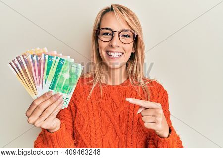 Beautiful blonde woman holding norwegian krone banknotes smiling happy pointing with hand and finger