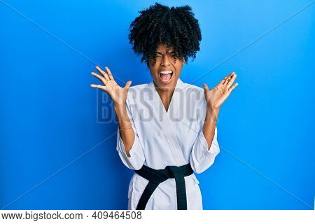 African american woman with afro hair wearing karate kimono and black belt celebrating mad and crazy for success with arms raised and closed eyes screaming excited. winner concept