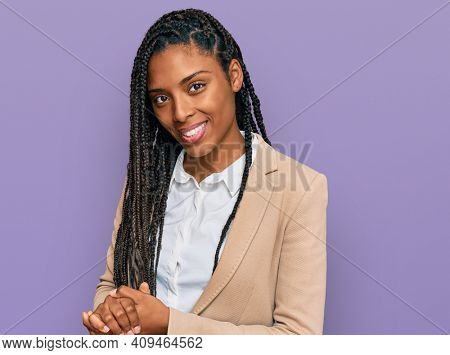 African american woman wearing business jacket with hands together and crossed fingers smiling relaxed and cheerful. success and optimistic