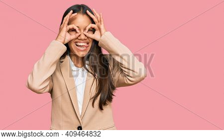 Beautiful hispanic woman wearing business jacket doing ok gesture like binoculars sticking tongue out, eyes looking through fingers. crazy expression.