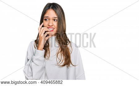 Young brunette woman wearing casual turtleneck sweater looking stressed and nervous with hands on mouth biting nails. anxiety problem.