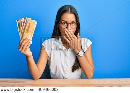 Beautiful hispanic woman holding 500 norwegian krone banknotes covering mouth with hand, shocked and afraid for mistake. surprised expression