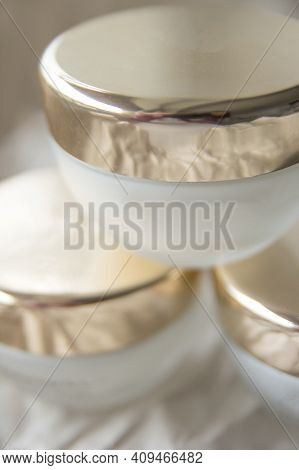 Close Up Set Of A Cream Jar. Three White Glass Skincare Cosmetic Jars With Golden Lid On Ivory Backg