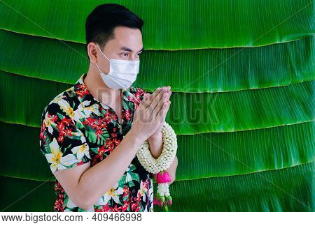 Thai Man Wearing Face Mask Doing Pay Respect Posture With Jasmine Garland On His Arm For New Normal