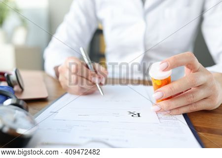 Doctor Writes Out Prescription And Holds Jar Of Pills In His Hands. Getting A Prescription For Medic