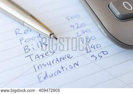 Monthly Expenses Are Listed In Notebook Next To Pen And Calculator. Income And Expense Control Conce