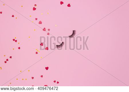 Artificial Eyelashes For Makeup On A Pink Background And Red Hearts. The Concept Of Eyelash Extensio