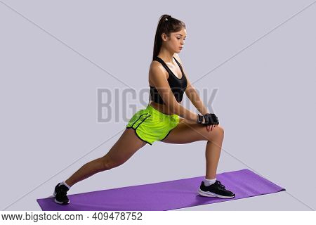 Flexibility And Stretching Concept. Profile View Of Young Caucasian Sportwoman Doing Yoga, Standing