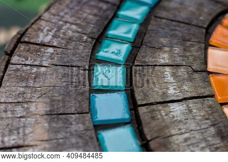 Mosaic Tiles On Round Cut Down Tree With Cracks Stump Outside Macro. Diy Garden Furniture, Decorated
