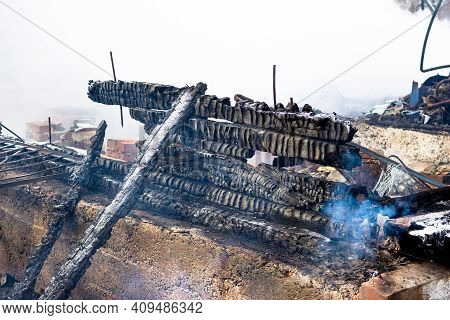 Burnt Walls Of A Wooden House After A Fire. Charred Planks And Smoke On The Ashes