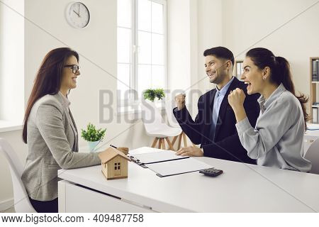 Young Couple Happy About Getting Approved For Mortgage Or Buying New House Or Flat