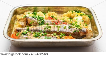 hake fish baked with vegetables close view, baking tray with tomatoes, broccoli and spices, home cooking