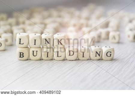 Link Building Words Written In Wooden Cubes Next To A Pile Of Other Letters. Backlinks Concept, Sear