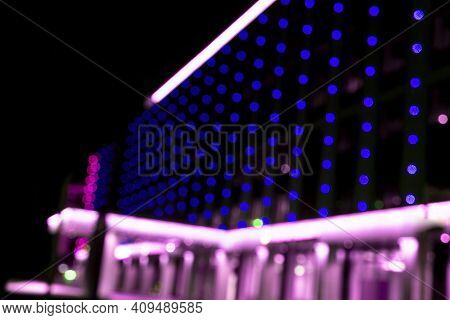 Blurred Office Building With Illuminated Facade Exterior At Night. Blurry Modern Business Building
