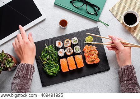 Woman Eating Sushi Takeaway At Work Desk Overhead. Eating Sushi For Lunch Break, Lunch Meal At Work,