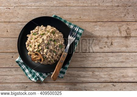 Risotto With Mushroom On Black Plate On Wooden Table. Top View. Copy Space