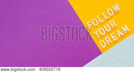 Diagonal Banner With Text Follow Your Dream On Purple, Yellow And Light Blue Background. Top View On