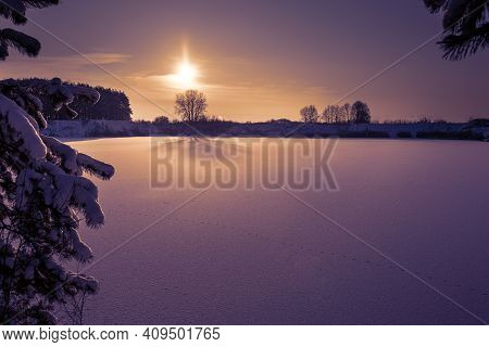 Wonderful Winter Landscape, Sunset Overlooking The Lake And Forest. Animal Tracks On A Frozen Lake.