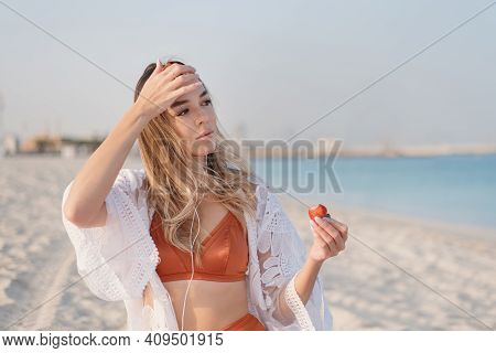 Young Blond Woman In Orange Bikini Standing At The Beach, Listening Music Via Earphones And Eating S