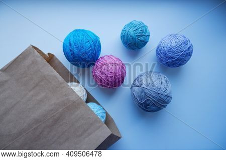 Colorful Balls Of Yarn In A Paper Bag On A White Background. Storage Of Yarn In An Eco-friendly Bag.