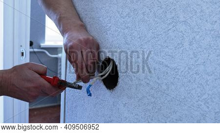 Hands Of An Electrician At Work On Preparing Wires For Replacing A Socket In An Apartment, Cutting O