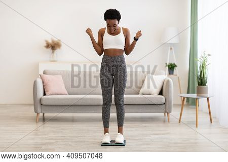 Great Weight Loss. Excited African American Woman On Weight-scales Shaking Fists In Joy Weighing Aft