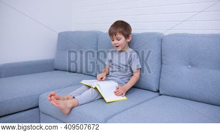 Little Boy In Gray Clothes Sitting On A Gray Sofa And Learning To Read A Yellow Book. Love For Readi
