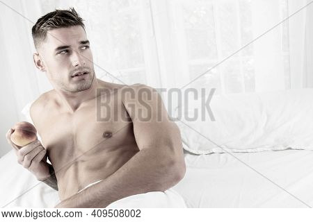 Sexy Muscular Man Lying Shirtless In Bed Revealing Pecs And Sixpack Abs Holding A Peach And Looking