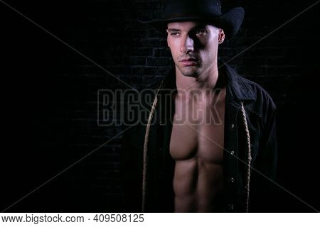 Portrait Of Handsome Cowboy Looking At Camera Wearing Hat With Open Black Shirt Revealing Defined Pe