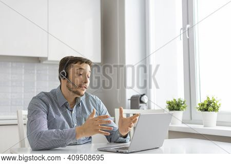 A Man During An Online Video Call. He Sits At Home In Front Of A Laptop Monitor And Talks Using A He