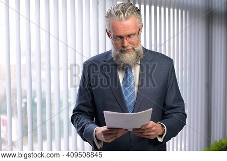 The Mature Gray-haired Company Executive Examines The Reports. The Boss Is Not Happy With The Perfor