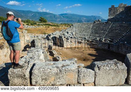 Man tourist standing on ruins of Theatre in Xanthos Ancient Lycia City and taking photo, Turkey. Sunny day, Old Lycian civilization heritage architecture amphitheater