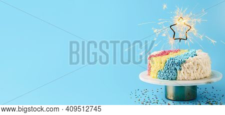 Shag Cake With Burned Sparkler Star On Blue Background. Colorful Shag Cake With Perfect Vanilla Butt