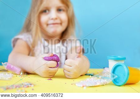 Blonde Girl Hold Purple Slime Isolated On A Blue Background. Child Playing With A Slime Toy. Making