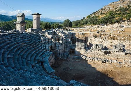 Ruins of amphitheater and Rock tombs in Xanthos Ancient City, Turkey. Sunny day, Old Lycian civilization heritage architecture