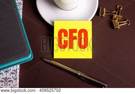 Cfo Chief Financial Officer Written On Yellow Paper On A Brown Background Near A Coffee Cup And Diar
