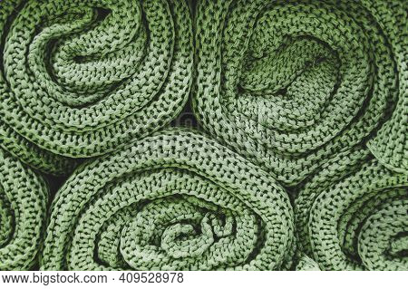 Green Knitted Blankets Rolled Into Rolls. Knitted Texture, Factory Textiles. Neat Pile Of Rolled Kni