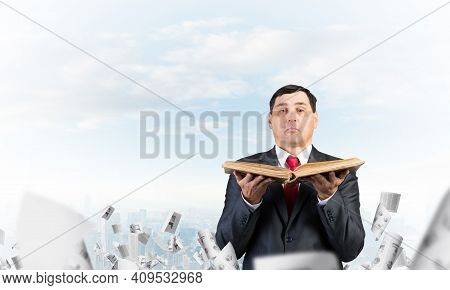 Serious Businessman Holding Open Book. Man In Business Suit Standing On Cloudy Cityscape Background