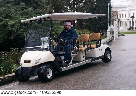 Yalta, Russia - January 26, 2021: Driver Of A Tourist Electric Golf Cart In A Christmas Hat Looks In