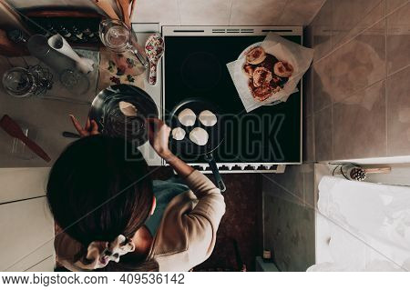 A Woman Prepares Pancakes On The Stove In The Kitchen. Top View Of Pancake Making Process. Pancakes