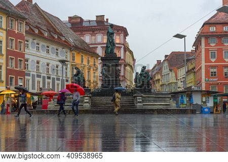 Graz/austria - June 22, 2019: People With Umbrella Passing By Erzherzog Johann Fountain At Hauptplat