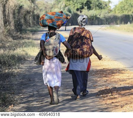 Two African Women With A Child And A Load Walk Along The Road. Black Women In Traditional Colored Cl