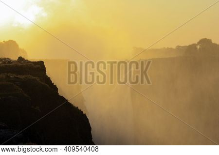 Sunrise Over The Mist And Water Dust Of Victoria Falls In Shades Of Red, Orange And Yellow. The Rays