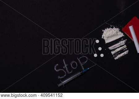 A Syringe And Drugs. On A Black Background, The Word Stop. International Day Against Drug Abuse And