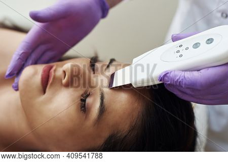 Woman Receiving Cleansing Therapy With A Professional Ultrasonic Equipment In Cosmetology Office. Pr