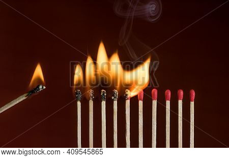 Lit Match Next To A Row Of Lighting Matches. Red Phosphorus Matches On Dark Red Background. Concept