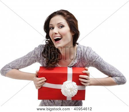 Laughing young woman hands a gift wrapped in red paper, isolated on white