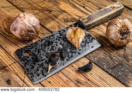 Fermented Bulbs And Cloves Of Black Garlic. Wooden Background. Top View