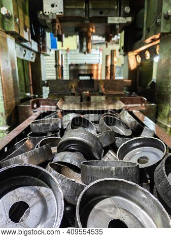 Pile Of Stamped Thick Sheet Black Metal Round Parts After A Hood Operation In Front Of Forming Press