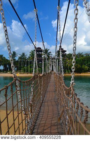 Suspension Bridge On Tropical Island. Sentosa Island, Singapore. Sea Scenery. Background For Vacatio